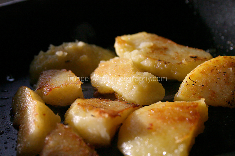 Potatoes cooking in a frying pan