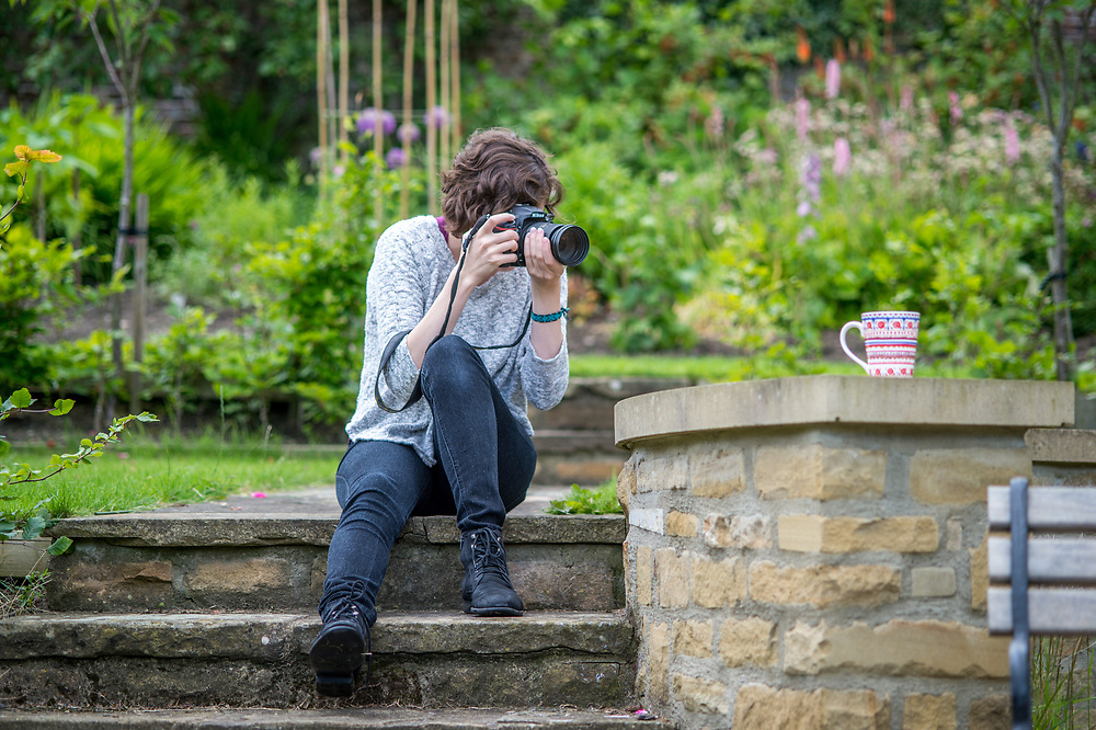 Young female photographer takes photo of mug, Richmond, Yorkshire, England
