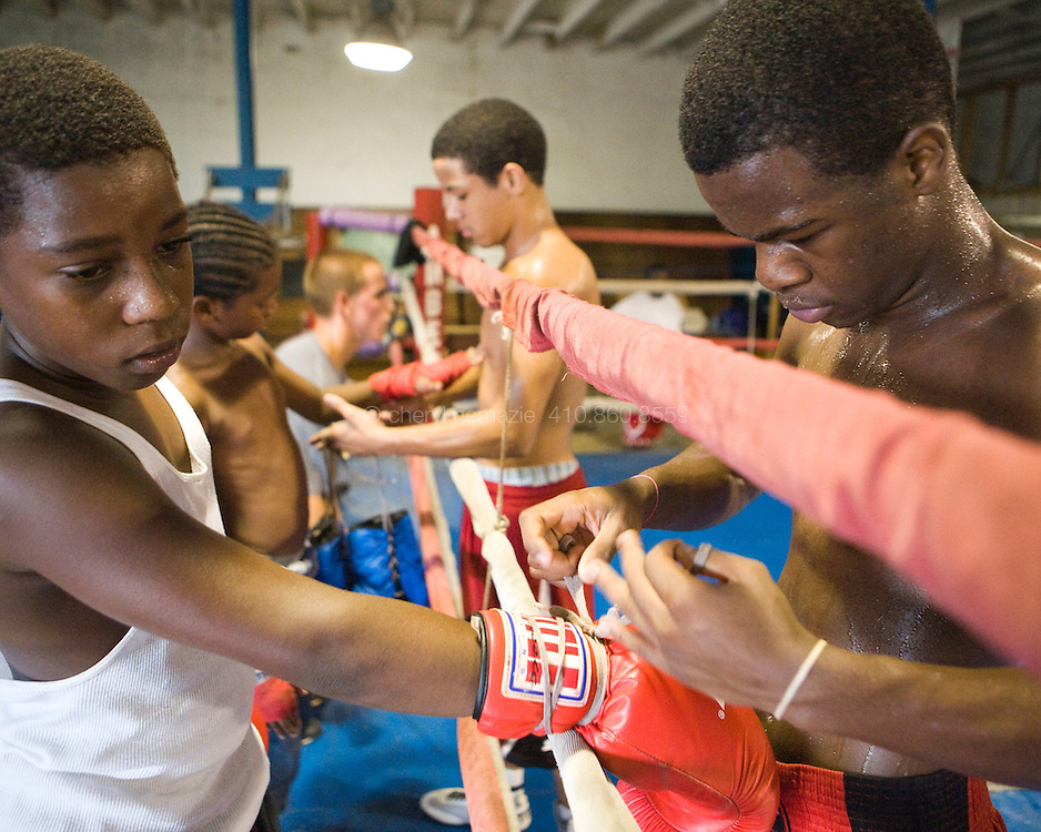 Older boxers wrap hands and tie gloves for the younger ones.