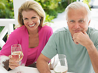 Couple holding wine glasses sitting at verandah table elevated view
