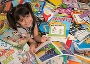 Jazlyn Cruz poses for a photograph with some of the books from her home library, January 19, 2017.