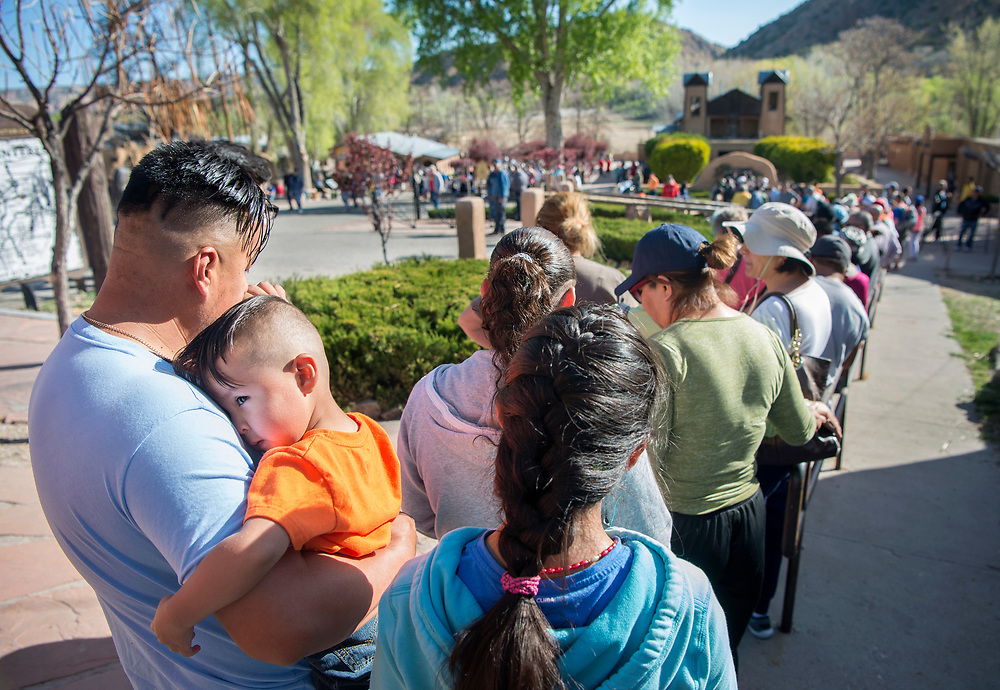em041417e/a/Angel Rios and his son Abraham, 2, from Espanola, wait in a long line to get into the Santuario de Chimayo, Friday April 14, 2017. With beautiful weather, thousands of people were making the Good Friday pilgrimage to the Northern New Mexico church.  (Eddie Moore/Albuquerque Journal