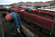 A Kurdish truck driver from Turkey at a yard with thousands of oil tanker trucks on their way to Iraq to bring Iraqi crude oil back to Turkey. Much of this oil export is illegal under UN sanctions against Iraq, but a blind eye has been turned toward the trade. The Kurds of Northern Iraq tax the transport of the oil through their territory. Turkey has been accused of cutting back on the trade in order to squeeze the Iraqi Kurds' unity, fearing independence claims from Turkey's own 12 million Kurds...Zakho, Iraqi Kurdistan. 01/12/2002...Photo © J.B. Russell