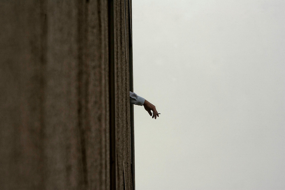 Barcelona, Catalunya, Spain.<br /> A man smoking in the window.&copy;Carmen Secanella.