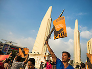 19 SEPTEMBER 2015 - BANGKOK, THAILAND:  An anti coup protestor at Democracy Monument in Bangkok. Hundreds of people protested against Thailand's military dominated government Saturday. The protest started with seminar about the 2006 coup that deposed popularly elected former Prime Minister Thaksin Shinawatra. After the seminar activists marched from Thammasat University to Democracy Monument, about 1 mile. Political gatherings of more than 5 people are banned by Thailand's military government and police tried to dissuade the protestors from finishing their march. Protestors ignored the police, who then stood by and watched but made no effort to intervene. At Democracy Monument protestors laid flowers and made speeches against the military. It was the largest anti-coup protest in Bangkok in more than a year.    PHOTO BY JACK KURTZ