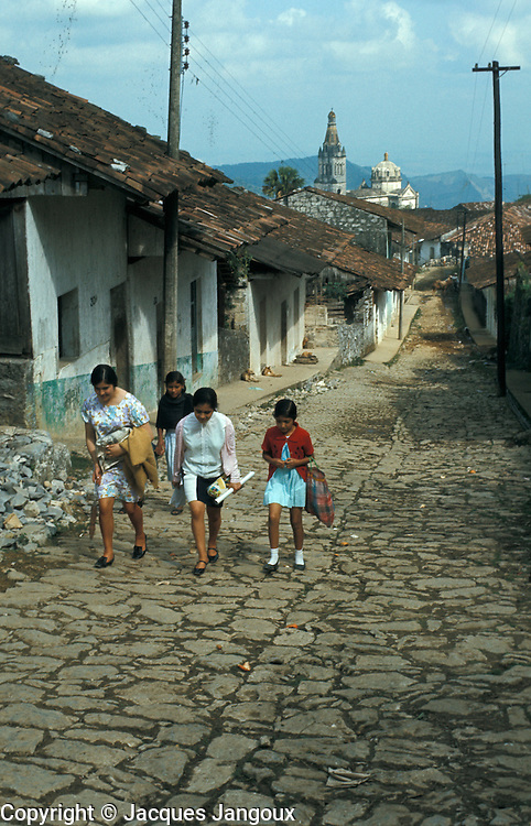 Women and girl on cobblestone street in village: Ixteped, Puebla Sate, Mexico.