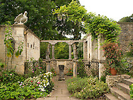 A stone paved area surround by walls and statues in the Peto Garden at Iford Manor in Bradford-on-Avon, Wilthire