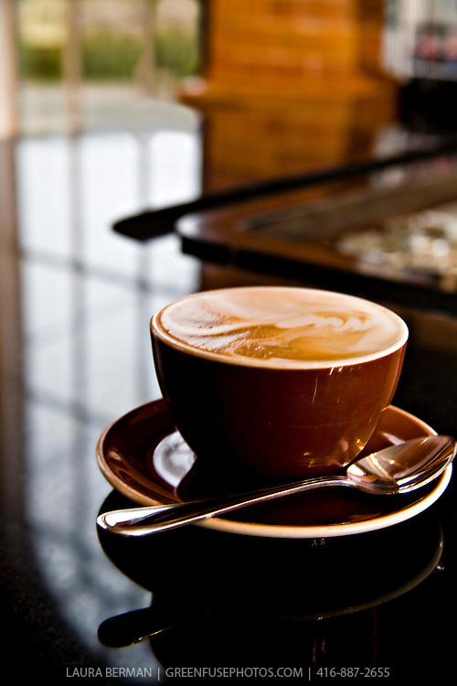 A coffee latte (cafe au lait) in a large brown cup and saucer on a black counter