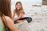 Two girls (10-12) playing in sand on beach  focus on girl in background