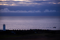Boat passing the Old Lower Lighthouse at dawn, Isle of Portland, Dorset, England, UK.