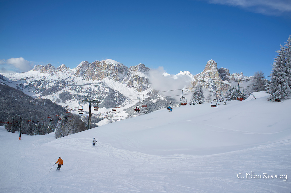 Skiers at the Alta Badia ski resort with Sassongher Mountain in the distance;  the Dolomites, South Tyrol, Italy