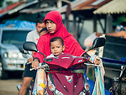 16 JUNE 2015 - NARATHIWAT, NARATHIWAT, THAILAND: A family on a motorcycle in a market in rural Narathiwat, Thailand.      PHOTO BY JACK KURTZ