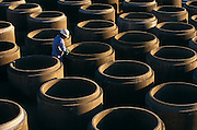 "Precast concrete pipes are prepared for distribution by a Mexican-born employee at Hanson Pipe & Products, Grand Prairie, Texas, USA. He cleans and inspects the tongue and groove seals of the upturned pipes wearing an obligatory hard hat and blue overalls. Precast concrete is made from a reusable mold or ""form"" and cured in a controlled environment, then transported to the construction site and lifted into place. Used in the construction of commercial building components, bridges, manholes and retaining walls, these products are the strongest pipe available, designed and plant tested to resist any load required with a design life of 70-100 years. .."