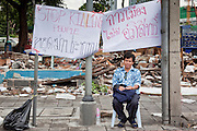 16 MAY 2010 - BANGKOK, THAILAND: A man sits under an anti government banner on Rama IV Road in Bangkok Sunday. Thai troops and anti government protesters clashed on Rama IV Road again Sunday afternoon in a series of running battles. Troops fired into the air and unidentified snipers shot at pedestrians on the sidewalks. At one point Sunday the government said it was going to impose a curfew only to rescind the announcement hours later. The situation in Bangkok continues to deteriorate as protests spread beyond the area of the Red Shirts stage at Ratchaprasong Intersection. Many protests now involve people who have not been active in the Red Shirt protests and live in the vicinity of Khlong Toei slum and Rama IV Road. Red Shirt leaders have called for a cease fire, but the government indicated that it is going to go ahead with operations to isolate the Red Shirt camp and clear the streets.      PHOTO BY JACK KURTZ