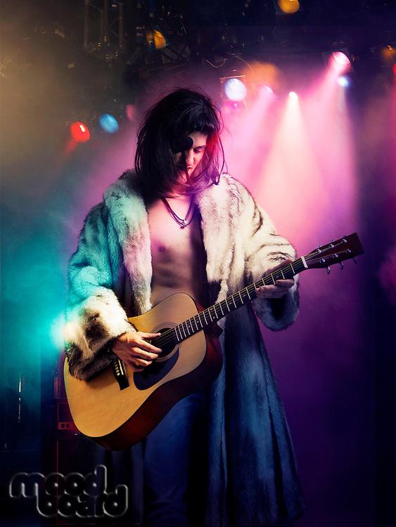 Young rock musician in fur coat playing guitar at concert