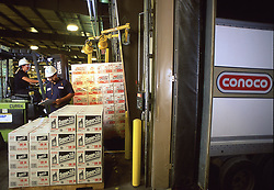 Stock photo of two men working in the an oil distribution warehouse lading and tracking shipments