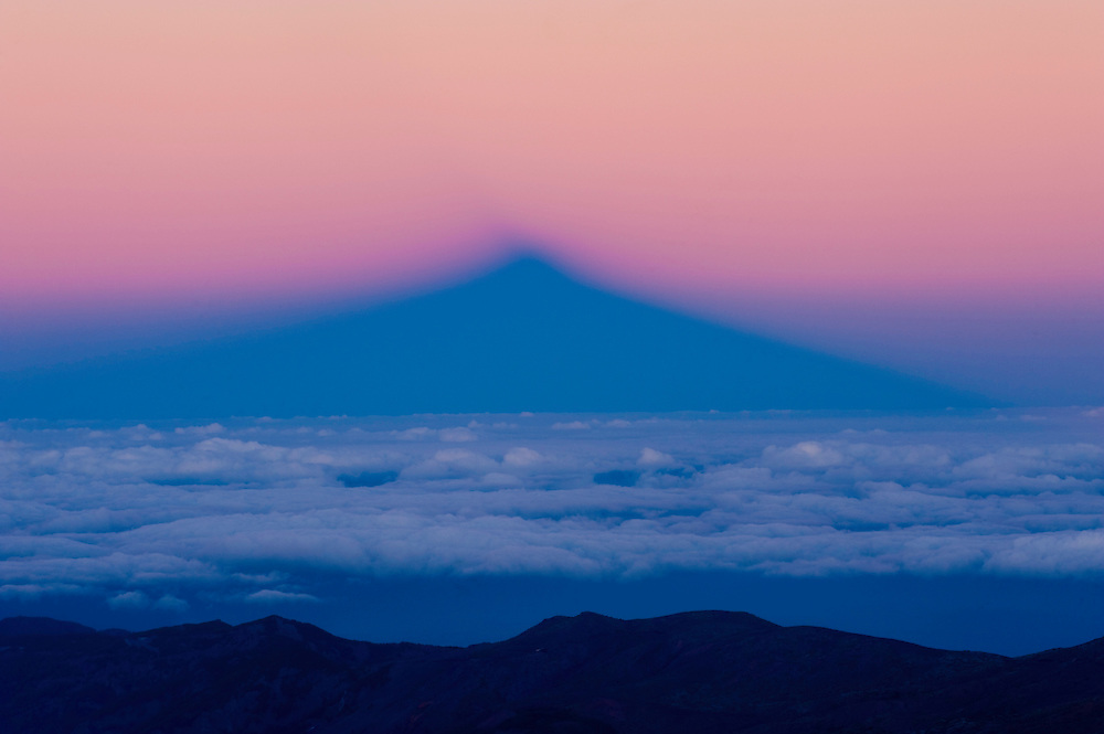 The Teide shadow in the clouds sea at sunset. The Teide volcano is (the highest mountain of Spain, 3.718 m). Teide National Park, Tenerife Island, Canary Islands, Spain.