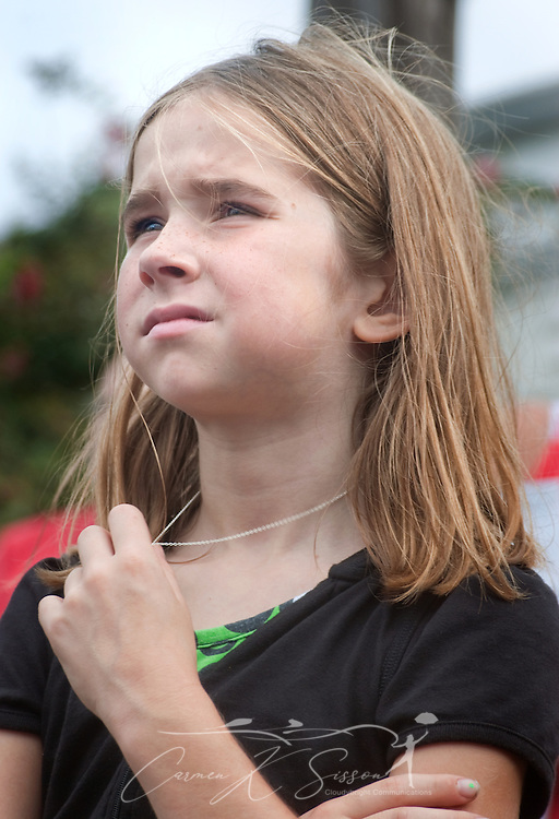 Mary Thames, 8, fondles a necklace as she listens during a ceremony commemorating the fifth anniversary of Hurricane Katrina Aug. 29, 2010 in Gulfport, Miss. Approximately 231 people died in Mississippi during the storm. (Photo by Carmen K. Sisson/Cloudybright)