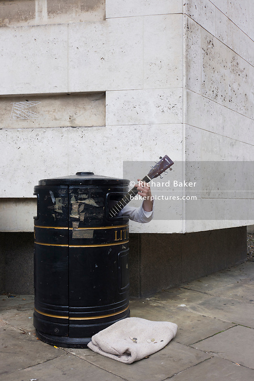A street busker hides in a litter bin to earn extra cash as passers-by hear his music on a Cambridge pavement.
