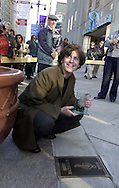 Eric Bazilian, singer, and Grammy nominated songwriter, is shown holding as he kneels over his plaque, after being inducted into Philadelphia's Walk of Fame, Friday, Nov. 17, 2000, in Philadelphia. (Photo by William Thomas Cain/www.photojournalist.cc)