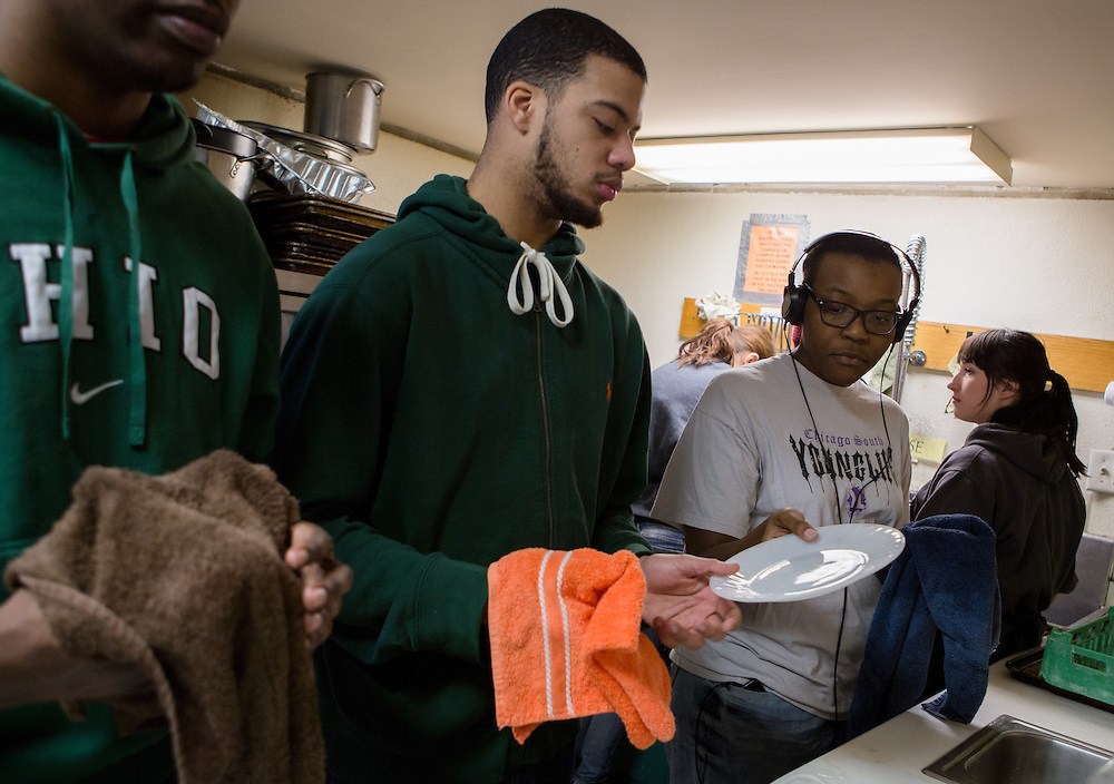 Ohio University student Canisha Russ passes a plate to Jordan Tyner, center, and Jerry Mobley, far left, as they help clean up the Ohio University United Campus Ministry kitchen on January 25, 2014, as part of the MLK Day of Service. Inclement weather caused the ministry to cancel the student-prepared meal that had been planned for the afternoon. Photo by Lauren Pond
