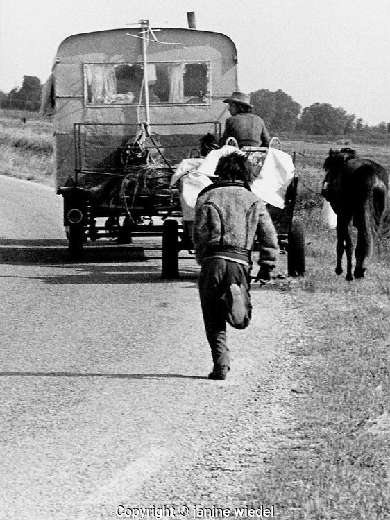 Young Gypsie boy running behind caravan in Southern France.