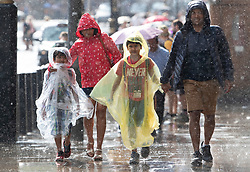 © Licensed to London News Pictures. 27/07/2018. London, UK. A family gets caught in a sudden downpour near Parliament as rain ends the long dry spell. Photo credit: Peter Macdiarmid/LNP