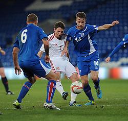 Joe Allen of Wales (Liverpool) takes a shot at goal under pressure from Kari Arnson (Rotherham United) of Iceland and Ragnar Sigurdsson (FK Kransnodar) of Iceland - Photo mandatory by-line: Dougie Allward/JMP - Tel: Mobile: 07966 386802 03/03/2014 -