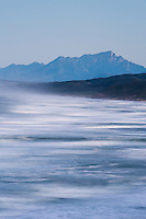 Blurred waves break along the coastline with the Outeniqua Mountains in the background, Goukamma Marine Protected Area, Western Cape, South Africa