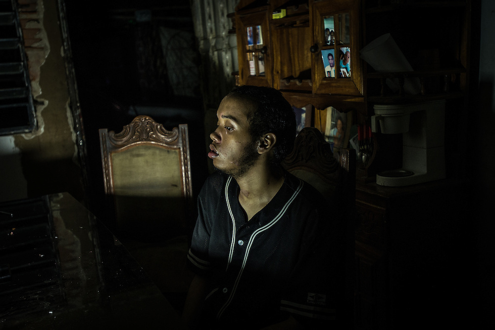"MARACAY, VENEZUELA - JULY 15, 2016: Schizophrenic Gerardo Simeone sits at the dinner table during a power outage, which are frequent in this town. He spends most of his days either sleeping, or standing in a corner in silence in his family's living room, rarely even making eye contact with members of his family.  His parents remember how he used to be when he was younger…before he became ill - recalling how affectionate and talkative he was. ""He was so kind and loving,"" said his mother, Evelin.  Gerardo's brother Accel is also schizophrenic. Their parents spend hours each week searching pharmacies for the psychiatric drugs that thier sons need, which are very difficult to find, because of nationwide shortages.  ""I am tired,"" Evelin said. ""This is too much sometimes"".  PHOTO: Meridith Kohut for The New York Times"