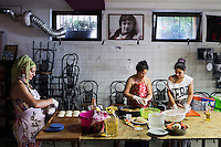 """ROME, ITALY - 3 JULY 2016: (L-R) Gipsy Queens members Codruta Balteau (24), Darmaz Florentina (33) and Maria Miglescu (20) prepare typical Roma dishes for their food stand at the iFest, an alternative music festival, here in the Astra 19 social center in Rome, Italy, on July 3rd 2016.<br /> <br /> The Gipsy Queens are a travelling catering business founded by Roma women in Rome.<br /> <br /> In 2015 Arci Solidarietà, an independent association for the promotion of social development, launched the """"Tavolo delle donne rom"""" (Round table of Roma women) to both incentivise the process of integration of Roma in the city of Rome and to strengthen the Roma women's self-esteem in the context of a culture tied to patriarchal models. The """"Gipsy Queens"""" project was founded by ten Roma women in July 2015 after an event organised together with Arci Solidarietà in the Candoni Roma camp in the Magliana, a neighbourhood in the South-West periphery of Rome, during which people were invited to dance and eat Roma cuisine. The goal of the Gipsy Queen travelling catering business is to support equal opportunities and female entrepreneurship among Roma women, who are often relegated to the roles of wives and mothers."""