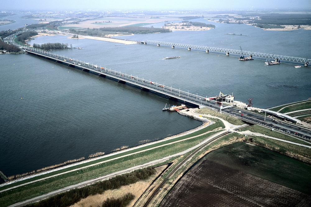 Nederland, Hollandsch Diep, 08-03-2002; in NO richting met Moerdijkbruggen, achter de vakwerk (spoor)brug de Nieuwe Merwede en begin Biesbos; linksboven water Dordtsche Kil; aan de  horizon (links vh midden): Dordrecht; HSl komt voor bestaande spoorbrug te lopen, zand voor spoordijk reeds aanwezig (links), bouw pijlers in het water; infrastructuur verkeer en vervoer spoor mobiliteit transport rivier binnenvaart landschap;<br /> luchtfoto (toeslag), aerial photo (additional fee)<br /> foto /photo Siebe Swart
