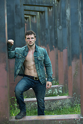 hot man in a denim jacket and no shirt leaning against steel