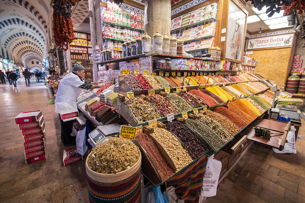 Male merchant setting up his corner market stall full of sweets and spices at the Istanbul Spice bazaar in Turkey
