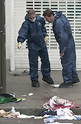 STABBING ON BRIXTON HIGH ST OUTSIDE WOOLWORTHS.LOOKING AT THE HANDLE OF THE KNIFE.PIC JAYNE RUSSELL.21.7.2002
