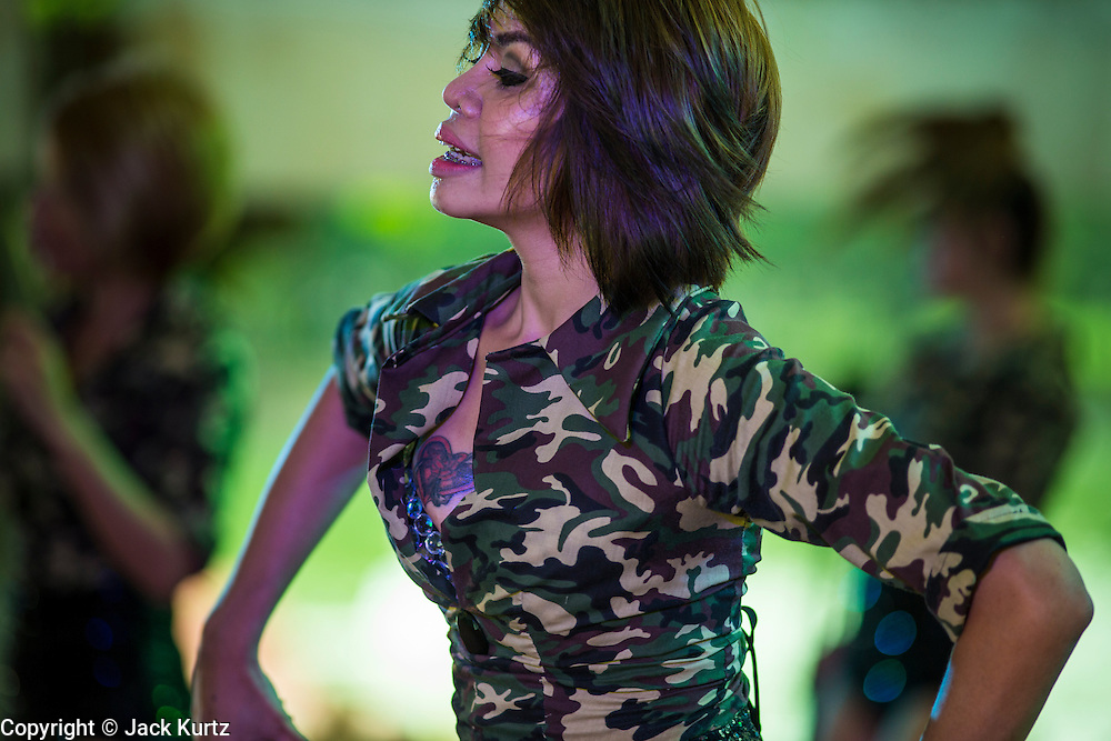 "15 JUNE 2014 - BANGKOK, THAILAND: A ""coyote dancer"" performs during a ""Return Happiness to Thais"" party in Lumpini Park in Bangkok. The Thai military junta, formally called the National Council for Peace and Order (NCPO), is sponsoring a series of events throughout Thailand to restore ""Happiness to Thais."" The events feature live music, dancing girls, military and police choirs, health screenings and free food.   PHOTO BY JACK KURTZ"