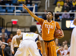 Jan 20, 2016; Morgantown, WV, USA; Texas Longhorns guard Isaiah Taylor (1) calls out a play while being defended by West Virginia Mountaineers guard Tarik Phillip (12) during the first half at the WVU Coliseum. Mandatory Credit: Ben Queen-USA TODAY Sports