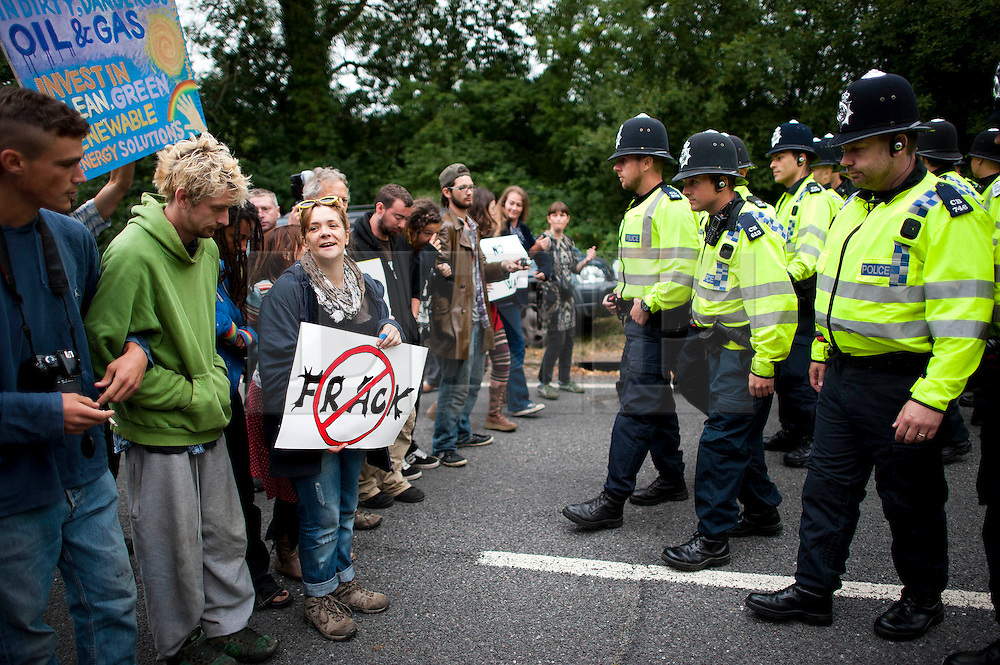 © London News Pictures. 16/08/2013. Balcombe, UK. Campaigners face up to police as they attempt to prevent a lorry entering the Cuadrilla drilling site in Balcombe, West Sussex which has been earmarked for fracking. Cuadrilla has temporarily ceased drilling at the site under advice from the police after campaign group No Dash For Gas threatened a weekend of civil disobedience. Photo credit: Ben Cawthra/LNP