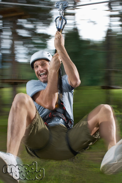 Man riding zip-line in forest