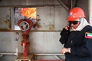 "Sara Akbar, development specialist for the Kuwait Oil Company, makes a cell phone call before joining firefighters from the companies (KWWK: Kuwait Wild Well Killers) as they prepare to extinguish the first oil well fire in Iraq's Rumaila Oil field. After dousing the flames with high pressure water hoses, they sealed the spurting well of gas and oil with drilling mud using what is called a ""stinger,"" a tapered pipe on the end of a long steel boom controlled by a bulldozer. Drilling mud, under high pressure, is pumped through the stinger into the well, stopping the flow of oil and gas. The Rumaila oil field is one of Iraq's biggest with five billion barrels in reserve. The burning wells in the Rumaila Field were ignited by retreating Iraqi troops when the US and UK invasion began in March 2003. Rumaila is also spelled Rumeilah."