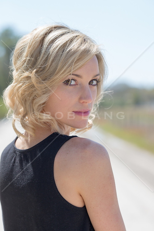 beautiful blonde woman outdoors on a dirt road