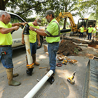 Mike Jackson, from left, Seth Johnson and Tommy Hood secure compression fitting to a new section of water line being installed along Knight Drive in Saltillo.