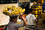 13 JUNE 2013 - YANGON, MYANMAR: A woman selling fresh bananas walks through the Annawa Fish Market. The Annawa Fish Market in Yangon is one of the largest fish markets in Myanmar. It serves as both a wholesale and retail market and serves both exporters and domestic customers. With thousands of miles of riverine waterways and ocean coastline Myanmar has a large seafood and fishing industry.    PHOTO BY JACK KURTZ