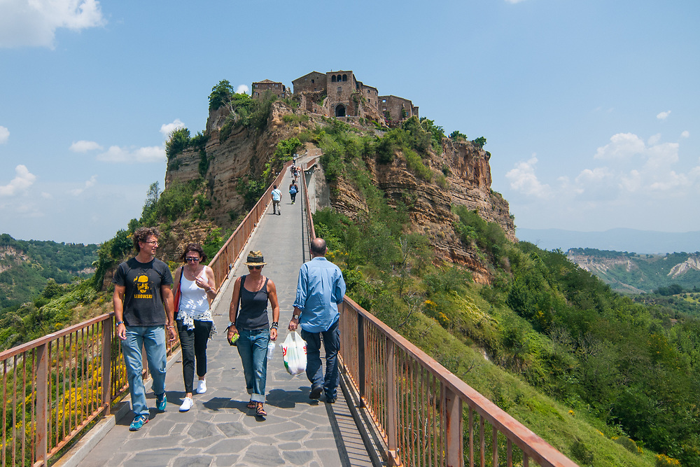 Tourists and citizen cross the bridge that leads to the village of Civita di Bagnoregio.<br /> Civita di Bagnoregio is a town in the Province of Viterbo in central Italy, a suburb of the comune of Bagnoregio, 1 kilometre (0.6 mi) east from it. It is about 120 kilometres (75 mi) north of Rome. Civita was founded by Etruscans more than 2,500 years ago. Bagnoregio continues as a small but prosperous town, while Civita became known in Italian as La citt&agrave; che muore (&quot;The Dying Town&quot;). Civita has only recently been experiencing a tourist revival. The population today varies from about 7 people in winter to more than 100 in summer.The town was placed on the World Monuments Fund's 2006 Watch List of the 100 Most Endangered Sites, because of threats it faces from erosion and unregulated tourism.