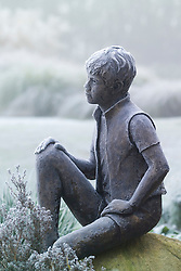 Frozen statue - 'Boy on a Rock' by Jane Hogben in John Massey's garden on a frosty winter's morning