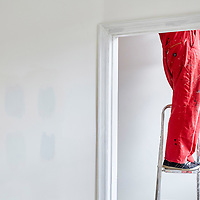 A photograph of a man wearing red overalls stood on ladders doing home improvement works at home