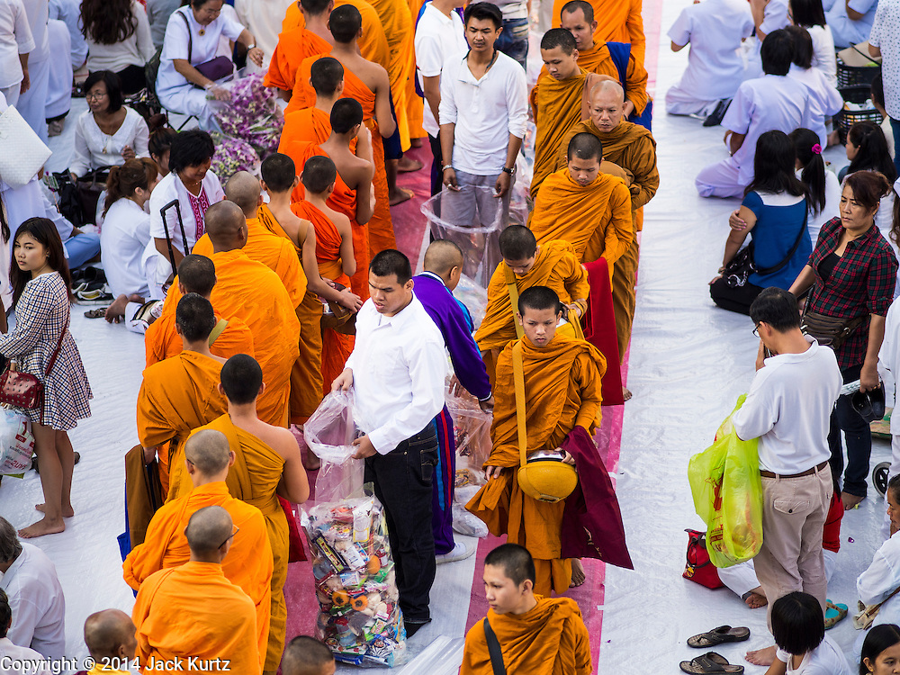 23 NOVEMBER 2014 - BANGKOK, THAILAND: People donate food and juice to Buddhist monks at a mass alms giving ceremony in Bangkok Sunday. 10,000 Buddhist monks participated in the ceremony on Rajadamri Road in front of Central World shopping mall. The alms giving was to assist Buddhist temples in the insurgency wracked southern provinces of Thailand, where Buddhist monks on their alms rounds have been targeted by Muslim extremists. The ceremony was sponsored by Wat Phra Dhammakaya, the center of the Dhammakaya Movement, a Buddhist sect founded in the 1970s. The temple has become active in Thai politics.     PHOTO BY JACK KURTZ