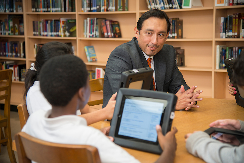 Principal Paul Zevallos poses for a photograph with students at McReynolds Middle School, December 6, 2013.