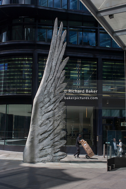 City workers pass-by the giant artwork of a bronze wing<br /> during a spring lunchtime in London's financial district, on 4th July, London, United Kingdom. As light reflects off nearby office buildings, the lunchtime crowd walk past this giant artwork on their way to meetings and sandwich bars. The ten-metre-tall bronze sculpture is by President of the Royal Academy of Arts, Christopher Le Brun, commissioned by Hammerson in 2009. It is called 'The City Wing' and has been cast by Morris Singer Art Founders, reputedly the oldest fine art foundry in the world.