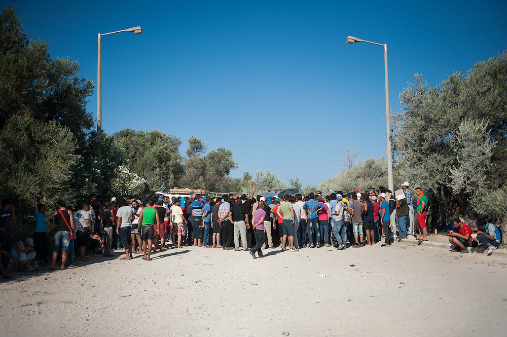 Refugees gather near two policemen at the entrance of Kara Tepe camp to hear their names. If their names are called they get the sought after permit to leave the island of Lesbos.